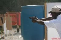 Ross Palmer shooting behind wall and barrels