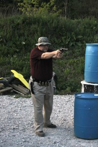 man in hat takes aim with a big revolver
