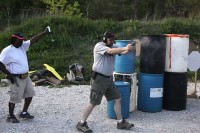 man shooting a single stack .45 cal 1911 pistol with muzzel flash and ejected round visible